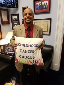Sam Abdelmessih in Congressman Michael McCaul's DC Office holding the Childhood Cancer Caucus pillow