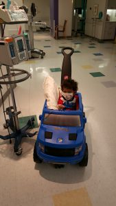 Gavin riding a toy car on the hospital floor.