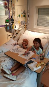 Gavin and Abbey hanging out in the hospital bed at Texas Children's Hospital.