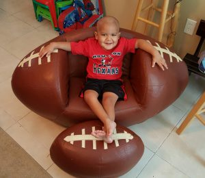 Gavin sitting in his football chair and Texan's shirt.